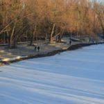Люди прогуливаются по деревянной набережной реки Везёлки в парке Победы